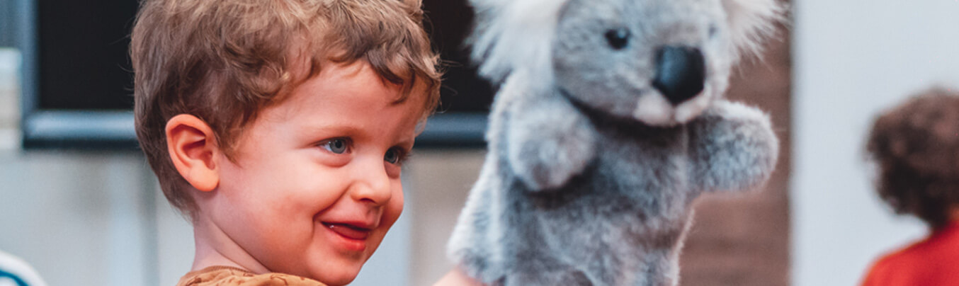 a child with a koala puppet