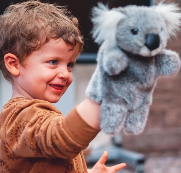 a child playing with a koala handpuppet